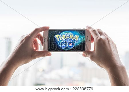 BANGKOK, THAILAND - February 1, 2018: Iphone smart phone gadget on hand with screen showing application Pokemon Go mobile gps game app developed by Niantic for iOS and Android devices