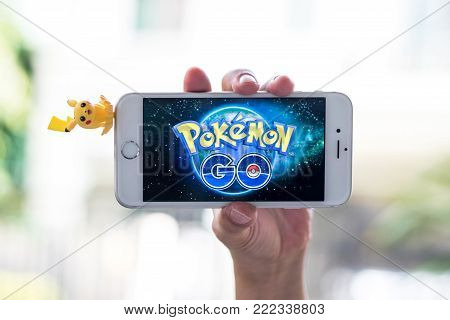 BANGKOK, THAILAND-January 17, 2018: Pokemon Go mobile game app on smart phone gadget on child kid hand with little Pikachu doll