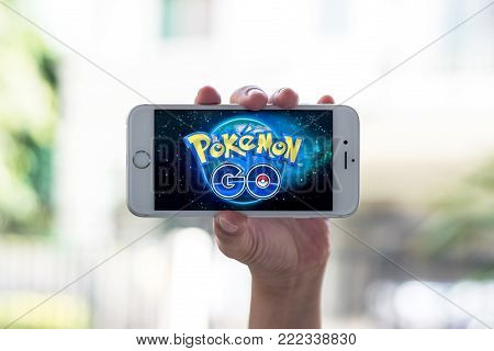 BANGKOK, THAILAND - January 29, 2018: Iphone smart phone gadget on hand with screen showing application Pokemon Go mobile gps game app developed by Niantic for iOS and Android devices
