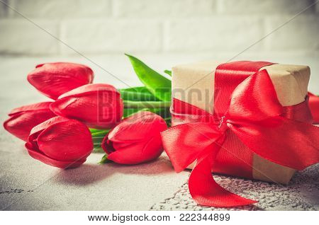 Bouquet of red tulips and gift box on white background. Spring flowers. Spring background. Greeting card for Valentine's Day, Woman's Day and Mother's Day. copy space.