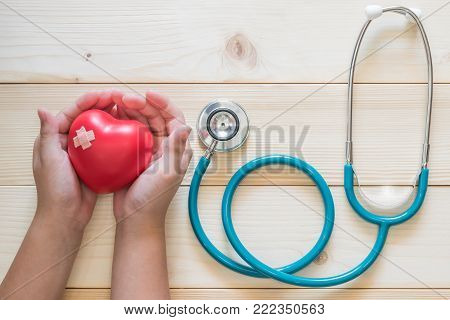 Pediatric care and child nursing healthcare service concept with kid patient's hands supporting red heart with medical stethoscope