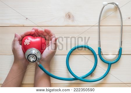 Children nursing pediatric care concept with kid patient's hands supporting red heart with medical doctor's stethoscope