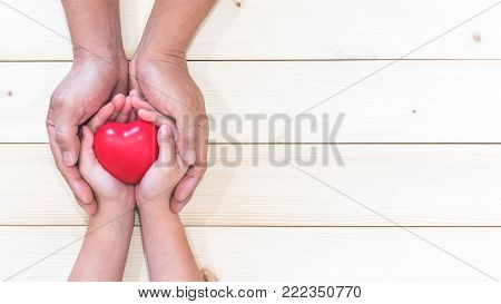 Parent supporting child's hands with red heart for I love you dad and Father's Day holiday celebration concept