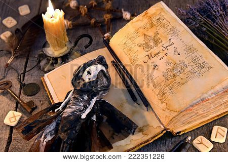 Old book with black magic spells, scary doll, rune and burning candle on planks. Occult, esoteric, divination and wicca concept. Halloween vintage background