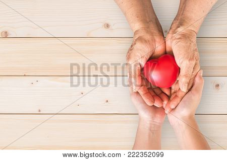 Elderly senior person or grandparent's hands with red heart  in support of nursing family caregiver for national hospice palliative care and family caregivers month concept