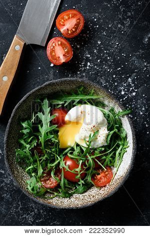 Healthy salad with arugula, tomatoes and poached egg in bowl on dark background. Top view with copy space for text