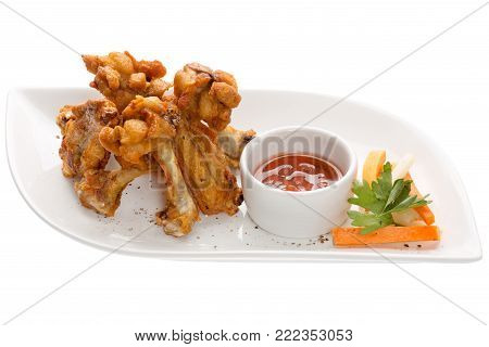 Chicken legs and wings slices in batter with spices and pepper to garnish: carrot, celery, greens, cucumber on a white plate foroforovoy on a white background. Tomato sauce in a gravy boat, oil