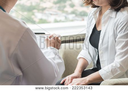 Doctor (obstetrician, gynecologist or psychiatrist) consulting and diagnostic examining woman patient's obstetric - gynecological health in medical clinic or hospital healthcare service center