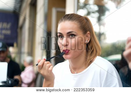Girl or woman eat with fork in cafe in paris, france. Food, snack, eating. Hunger, appetite concept.
