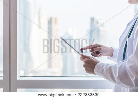Doctor or physician holding mobile tablet working on patient's health record in medical clinic office or hospital with city office building background for online healthcare assistance service concept
