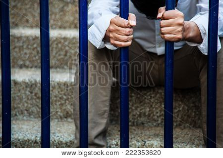 A man in blue collar shirt and black slacks behind the iron fence, Hand holding iron fence with a sense of hopelessness, sadness, solitude, sorrow, failure, melancholy and isolation.
