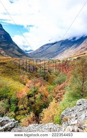 Glencoe at the meeting of the waters with the Three Sisters in background at spectacular fall season with cloudy sky background. Multicolored outdoors vertical image. Uk, Scotland.