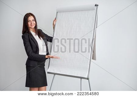beautiful business woman showing a business team information on the flipchart.