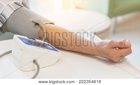 Patient checking up blood pressure using upper arm blood pressure measuring monitor medical equipment in clinic examination room