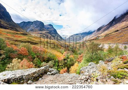Glencoe at the meeting of the waters with the Three Sisters in background at spectacular fall season with cloudy sky background. Multicolored outdoors horizontal image. Uk, Scotland.