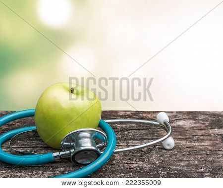 World health day concept with green natural nutrient apple with doctor's stethoscope