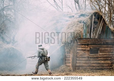Re-enactor Dressed As German Wehrmacht Infantry Soldier In WW II Running On Battlefield Near Burning Wooden House.