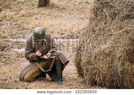 Re-enactor Dressed As Russian Soviet Infantry Soldier Of World War II Reloading Rifle Weapon.
