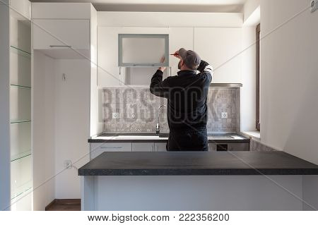 Carpenter working on new kitchen. Handyman fixing a door in a kitchen
