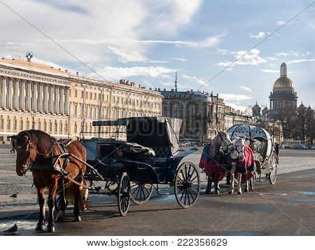 A coach and a cabriolet with horses harnessed in them stand on the Palace Square on the background of the St. Isaac's Cathedral and the General Staff Building in St. Petersburg