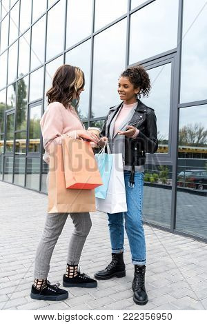 young stylish shopping buddies with paper bags talking outdoors