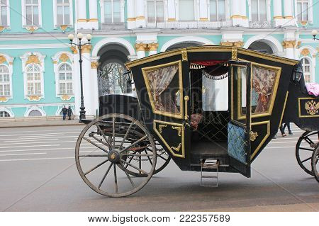 Old Retro Carriage in Front of Winter Palace (Hermitage Museum) on Palace Square in St. Petersburg, Russia. Historical Old-Fashioned Transport, Horse-Drawn Empty Vehicle on Downtown City Street.