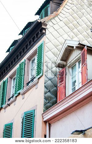 French provencal style vibrant multicolored houses with wooden shutters and tile in France, Alsace region. Vibrant outdoors vertical image.