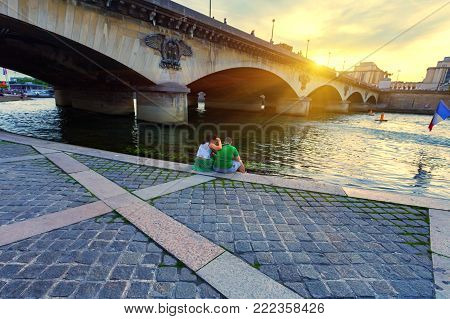 PARIS, FRANCE - CIRCA JUNE 2014: Romantic young couple sitting on bank of Siene with setting sun, back view