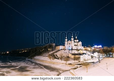 Vitebsk, Belarus. Famous Landmark Is Assumption Cathedral Church In Upper Town On Uspensky Mount Hill Under Winter Night Starry Sky. Historic Heritage And Frozen River Western Dvina