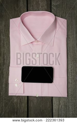 Pink shirt and mobile on wooden background. Top view.