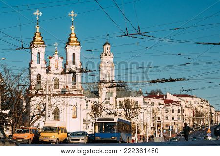 Vitebsk, Belarus. Traffic At Lenina Street And Landmarks On Background Church Of The Resurrection Of Christ On The Market Square And City Hall In Sunny Winter Day