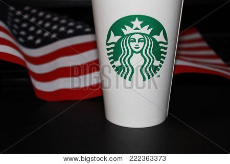 MOSCOW, RUSSIA - JANUARY 11, 2018: Starbucks Coffee White Paper Cup for Take Away Drinks with American Flag on Black Table. Starbucks Corporation is an American Coffeehouse Company Famous Worldwide.