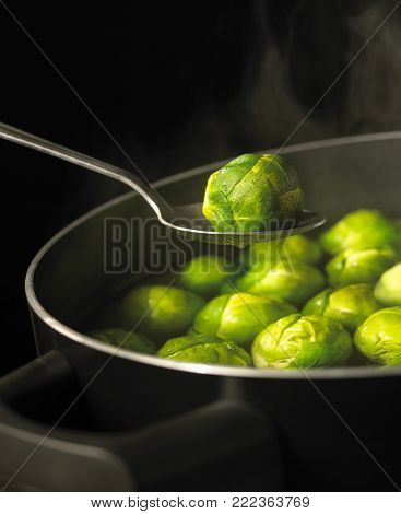 SPOON HOLDING BRUSSELS SPROUT OVER PAN OF BOILING WATER FULL OF SPROUTS WITH RISING STEAM SIMMERING ON GAS COOKER