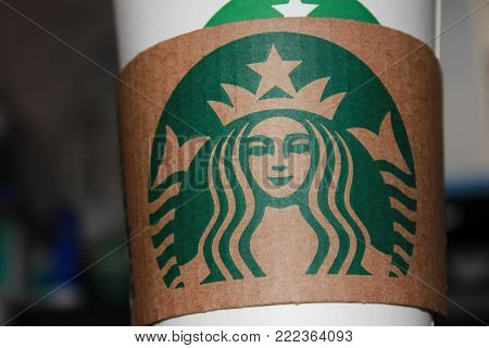 MOSCOW, RUSSIA - JANUARY 11, 2018: Starbucks Coffee Brand Logo Close Up on Paper Cup Sleeve. Starbucks Corporation is an American Coffee Shop Company and Coffeehouse Chain, Founded in Seattle in 1971.