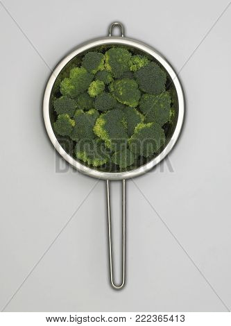 STAINLESS STEEL COLANDER CONTAINING FRESH BROCCOLI FLORETS