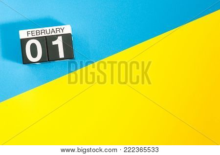 February 1st. Day 1 of february month, calendar on blue and yellow background flat lay, top view. Winter time. Empty space for text.