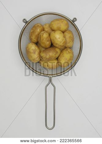 STAINLESS STEEL SIEVE CONTAINING FRESH POTATOES ON WHITE BACKGROUND
