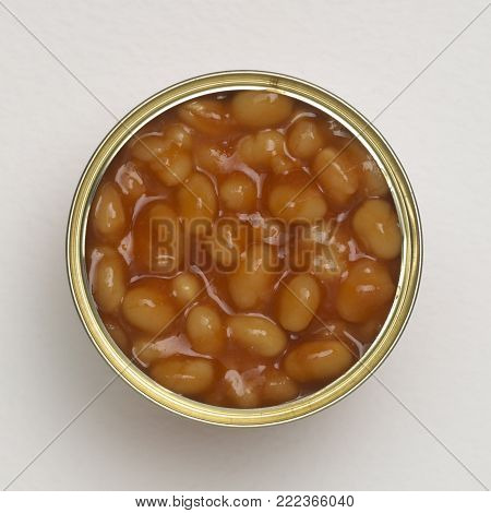 OPEN TIN OF BAKED BEANS CLOSE UP ON WHITE BACKGROUND