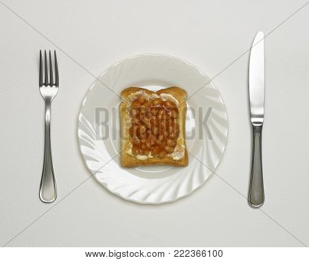BAKED BEANS ON TOAST ON WHITE PLATE WITH KNIFE AND FORK