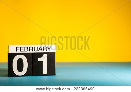 February 1st. Day 1 of february month, calendar on yellow background. Winter time. Empty space for text.