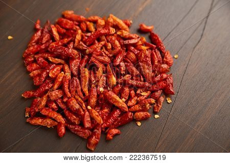 Red hot chili peppers outdoors. Close-up bunch of red peppers. From above pile of red pepper placed on dark board background. pepper, red, spicy, hot, mexico, chili, food