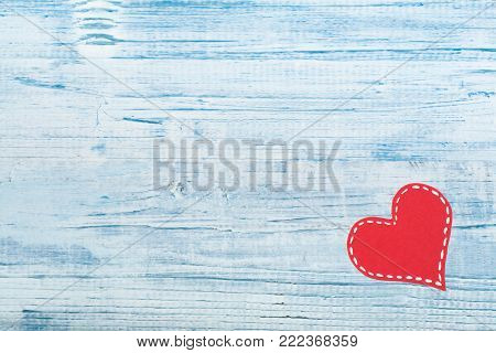 Red paper hearts on a blue wooden background. Valentine's Day. Copy space. Top view.