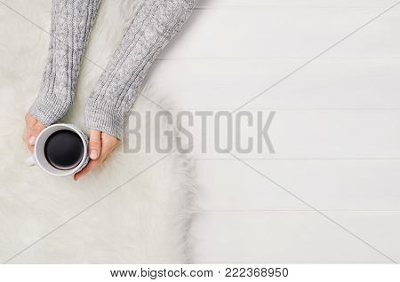 Female hand holding a cup of coffee on white wooden table. Winter or christmas cosy nordic, scandinavian background. Photograph taken from above, top view with copy space