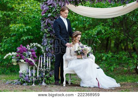 Young beautiful groom in dark blue suit and bride in white crop top dress and holding big wedding bouquet with lilac and long ribbons. Happy couple on spring wedding walk.