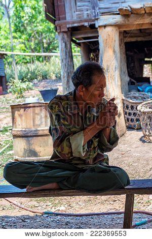 BANGKOK, THAILAND - CIRCA MARCH 2013: Unidentified countryman on bench lighting a sigarette