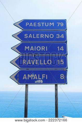 Amalfi coast road sign blue plate on sea background