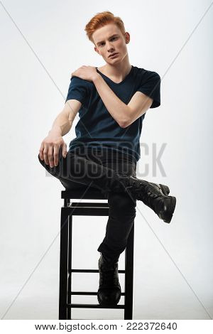 Well-built. Good-looking unsmiling well-built young man sitting on the chair and putting one foot on it and having his hands on his shoulder and knee