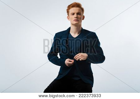 Grim. Good-looking unsmiling red-haired young man wearing a black jacket and buttoning it up and staring