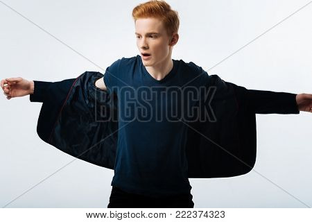 Getting undressed. Attractive earnest red-haired young man taking his jacket off and having his mouth opened and looking in the distance