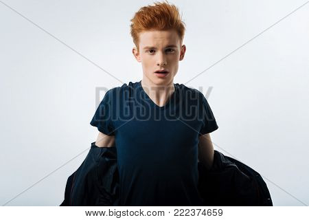 Taking off. Attractive stony-faced red-headed young man taking off a black jacket and having a stylish haircut and having his mouth opened